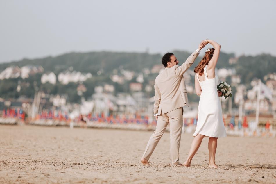 un couple de maries qui danse sur la plage de deauville